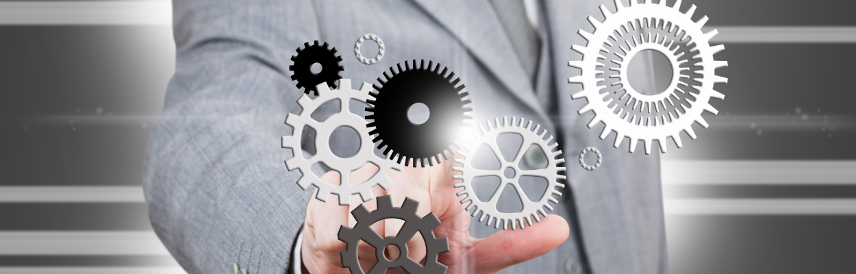 business man pointing at set of gears